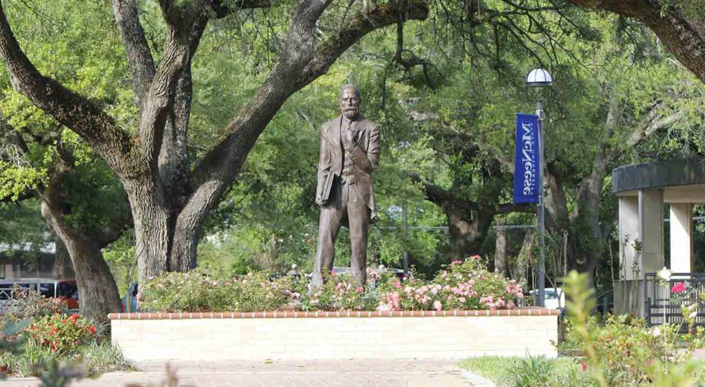 A statue of John McNeese surrounded by greenery and flowers on campus
